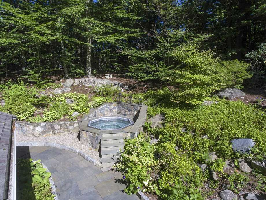 The tiered backyard features professional landscaping, perennial gardens, a bluestone patio and built-in hot tub. / Dennis M.Carbo