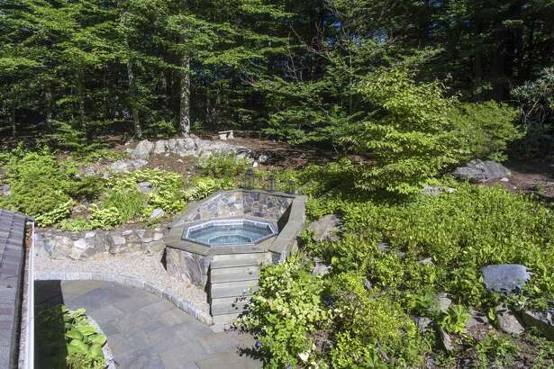 The tiered backyard features professional landscaping, perennial gardens, a bluestone patio and built-in hot tub.