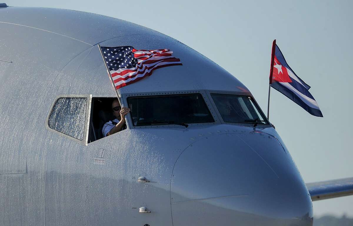 TOPSHOT - An American Airlines plane fluttering US and Cuba national flags is seen uppon arrival at Jose Marti International Airport becoming the first Miami-Havana commercial flight in 50 years, coinciding with the beginning of the tributes to late Cuban leader Fidel Castro, on November 28, 2016 in Havana. / AFP PHOTO / YAMIL LAGEYAMIL LAGE/AFP/Getty Images