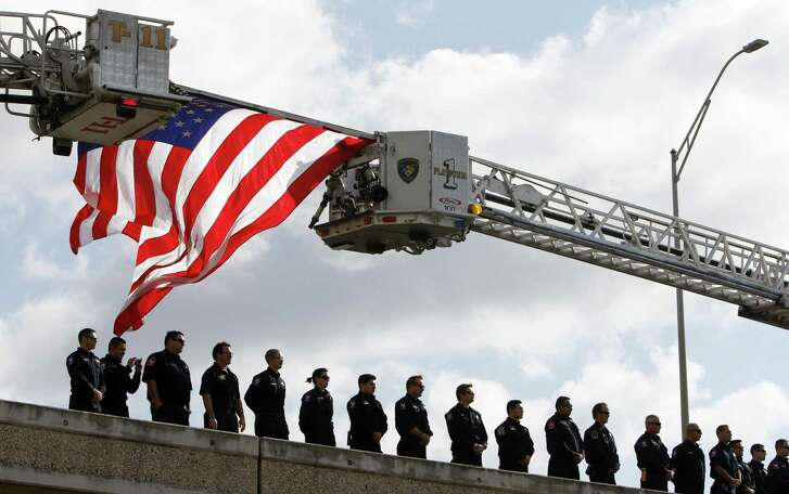 Firefighters at an overpass of U.S. 281 near Alamo Stadium await the procession for Marconi from Porter Loring Mortuary near downtown to Community Bible Church on Loop 1604.