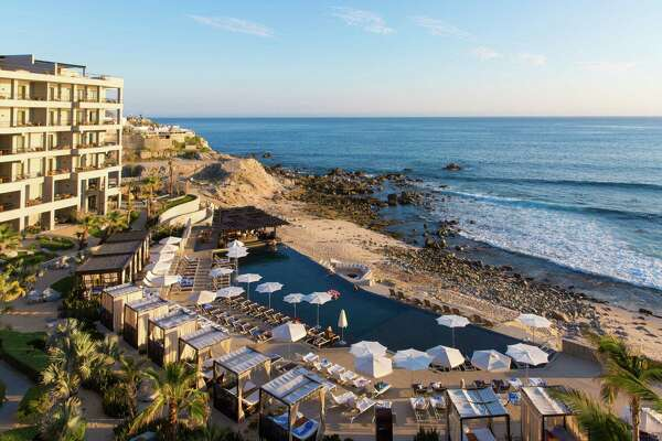 The sleek cape hotel's infinity pool offers views of monuments beach and the cabo arch.
