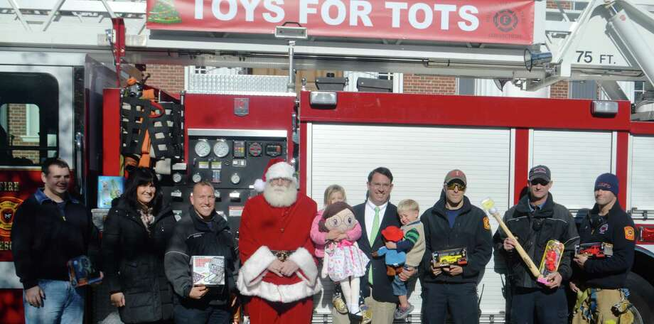 Milford Professional Firefighters joined Santa and Mayor Benjamin Blake last week at City Hall to officially kick-off the 2016 Toys for Tots drive in Milford. The mayor, center, is holding two of his three children. Photo: Contributed Photo / Connecticut Post