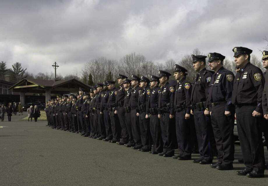 FILE - Police officers from Stamford and area departments stand at attention outside St. Leo's Church while waiting for the funeral procession for Stamford Police officer Marcia Lynn Stella to leave the church. Photo: Andrew Sullivan/Staff Photo / 00005891A