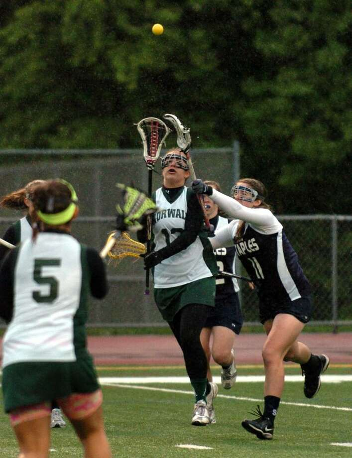 Staples' #11 Blair Barone, right, looks to block a pass by Norwalk's #13 Sara Costa to teammate #5 Marcella Libertino, during girls lacrosse action in Norwalk, Conn. on Tuesday May 18, 2010. Photo: Christian Abraham / Connecticut Post