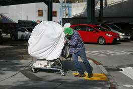 Oscar McKinney struggles to push cart up a curb along 13th Street on the way to the laundromat to wash his laundry on Monday, November 28 2016 in San Francisco, California.