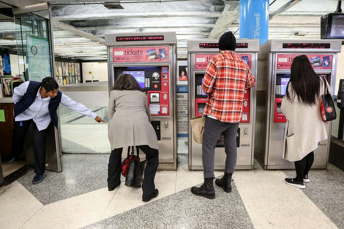 A Muni attendant helps as passengers purchase Muni tickets from kiosks at Powell Station on Monday, November 29, 2016.