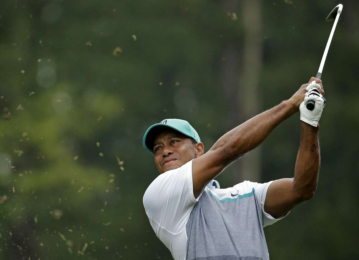 FILE - In this Aug. 20, 2015, file photo, Tiger Woods watches his shot on the 12th hole during the first round of the Wyndham Championship golf tournament in Greensboro, N.C. Tiger Woods returns to competition, and Ernie Els is more curious about his head than any of his back surgeries that kept him out 15 months. (AP Photo/Chuck Burton, File)