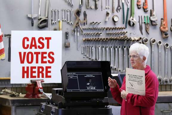 Poll worker Cathy Machacek waves over voters to the electronic ballot box at the Department of Public Works garage on Election Day, Tuesday, Nov. 8, 2016, in Slinger, Wis. (John Ehlke/West Bend Daily News via AP)