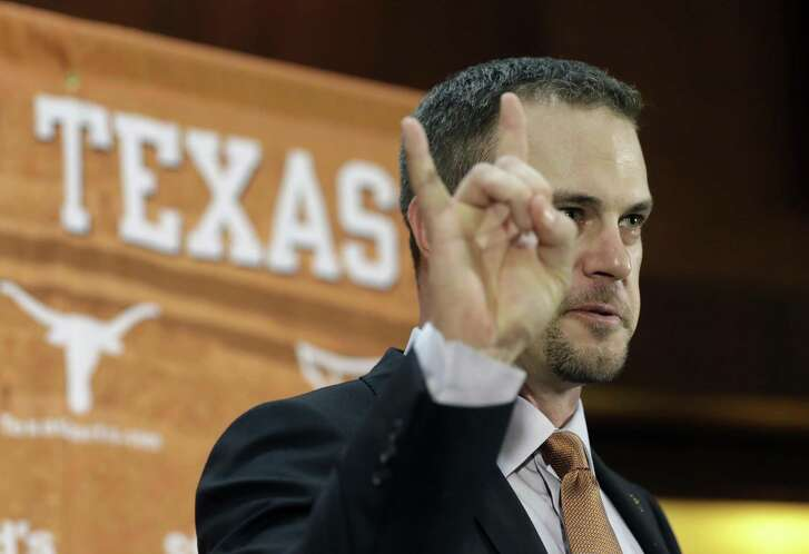 """Tom Herman holds up the """"Hook 'em Horns"""" sign during a news conference where he was introduced as Texas' new coach on Nov. 27, 2016, in Austin."""