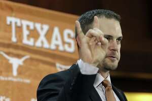 "Tom Herman holds up the ""Hook 'em Horns"" sign during a news conference where he was introduced as Texas' new coach on Nov. 27, 2016, in Austin."