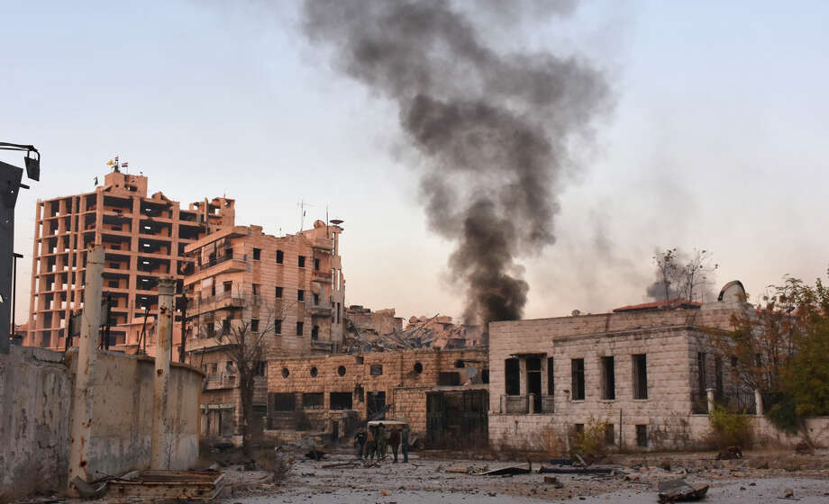 Smoke billows over a bombed-out neighborhood Monday in Aleppo during Syrian government forces assault to retake the entire city from rebel fighters. Photo: GEORGE OURFALIAN, Stringer / AFP or licensors