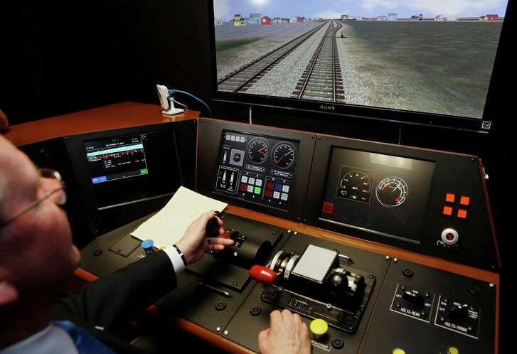 FILE - In a  Feb. 20, 2014 file photo, Metrolink Director of Operations, R.T. McCarthy, demonstrates Metrolink's implementation of Positive Train Control, (PTC) at the Metrolink Locomotive and Cab Car Simulators training facility in Los Angeles' Union Station.  Federal regulators said Monday, Nov. 28, 2016. The nation's three busiest commuter railroads, The Long Island Rail Road, New Jersey Transit and Metro-North, continue to lag behind their smaller West Coast counterparts in installing sophisticated train-control technology that's seen as an antidote to crashes involving speeding and other human factors.  (AP Photo/Damian Dovarganes, File)