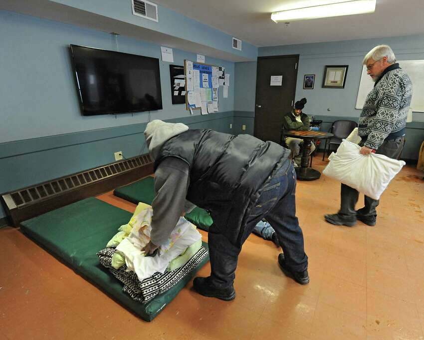 Staff member Anthony Mayers, left, and Tom McCrossan, director of the men's shelter, set up bedding in the overflow TV room at the City Mission on Thursday, Feb. 19, 2015 in Schenectady, N.Y. (Lori Van Buren / Times Union)