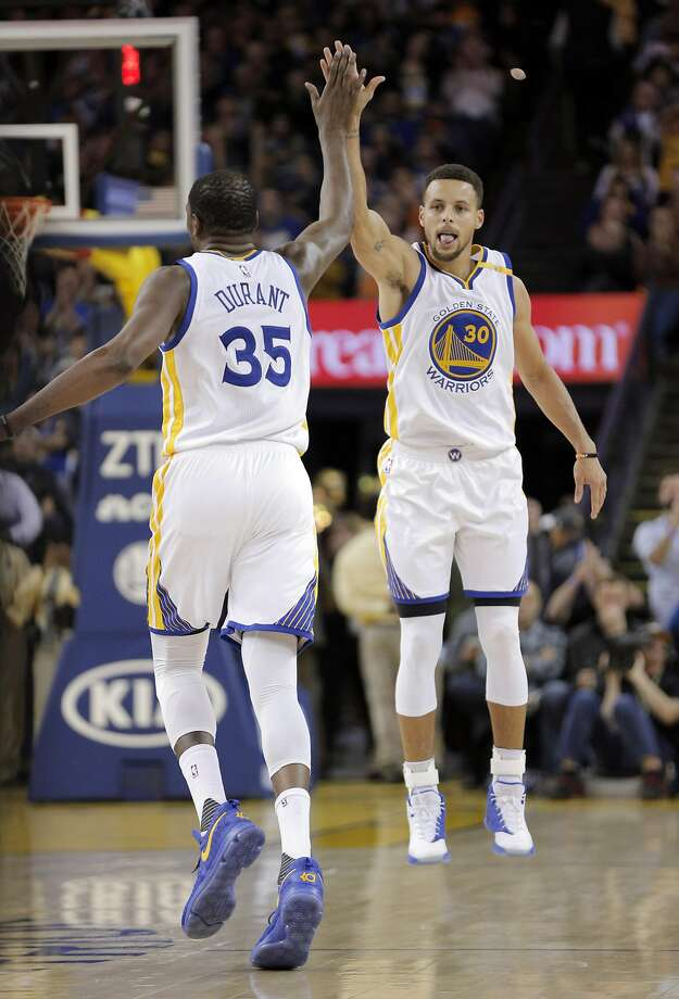 Stephen Curry (30) and Kevin Durant (35) celebrate a three pointer by Curry in the second half as the Golden State Warriors played the Atlanta Hawks at Oracle Arena in Oakland, Calif., on Monday, November 28, 2016. The Warriors won 105-100. Photo: Carlos Avila Gonzalez, The Chronicle