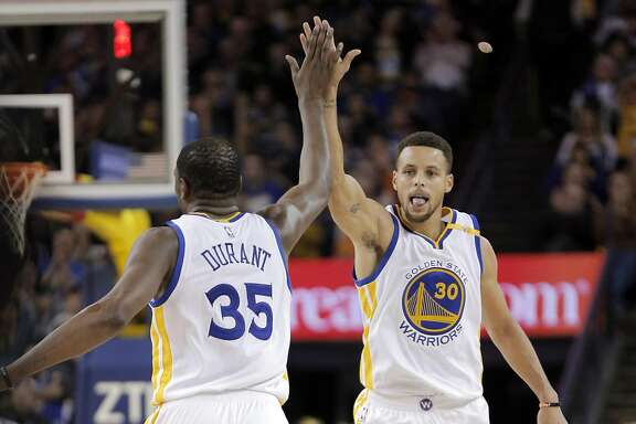 Stephen Curry (30) and Kevin Durant (35) celebrate a three pointer by Curry in the second half as the Golden State Warriors played the Atlanta Hawks at Oracle Arena in Oakland, Calif., on Monday, November 28, 2016. The Warriors won 105-100.