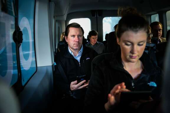 Kevin Eckert (center) and Megan Parker (right) are seen riding in a Chariot commuter-van on their way to work, in San Francisco, California, on Monday, November 28, 2016.