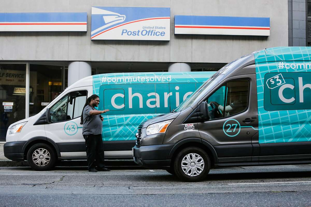 Vincent Jones (left), a driver for Chariot commuter-van service waves to another Chariot van passing by, in San Francisco, California, on Monday, November 28, 2016.
