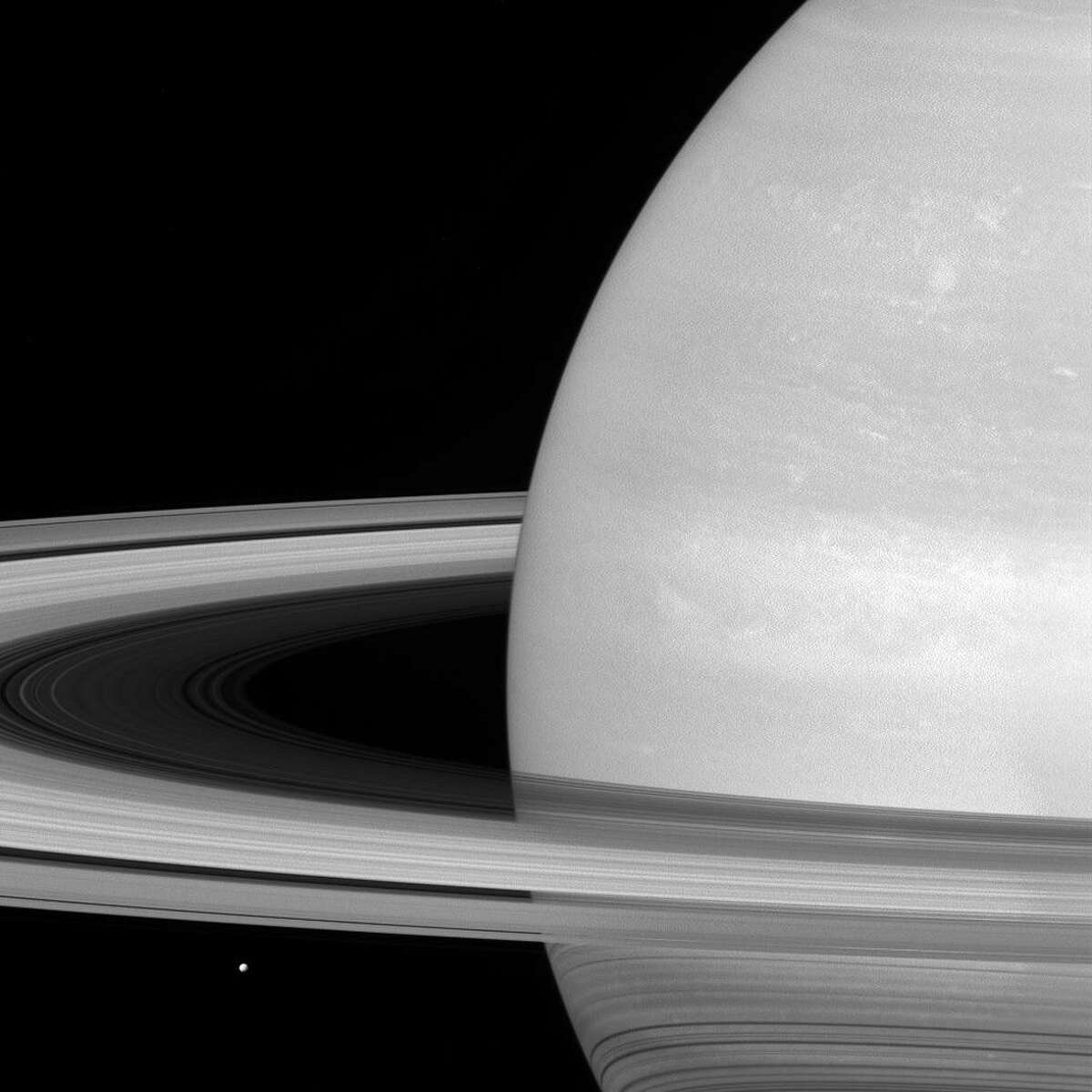 NASA caption: Saturn's icy moon Mimas is dwarfed by the planet's enormous rings.
