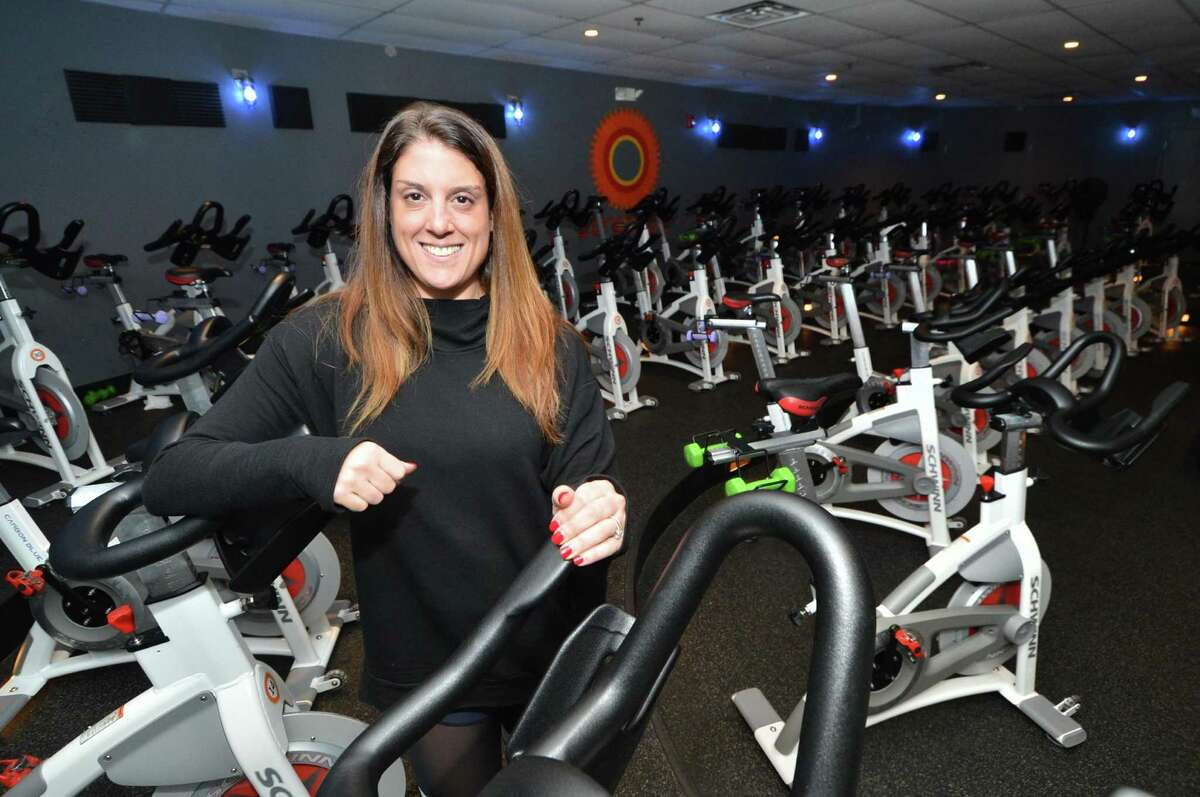 Above, owner Amy Hochhauser stands near some of the 46 bikes in her JoyRide Cycling and Fitness Studio, below, on Monday in Westport.