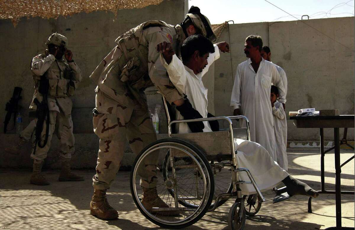 Texas National Guardsman Pfc. James Green searches Qasim Ahyab Ahmed at the Camp Danger Horse gate in Tikrit, Iraq, Sunday, September 25, 2005. Nicole Fruge/San Antonio Express News