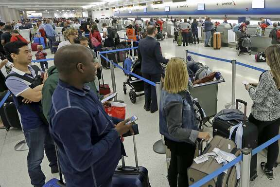 Passengers stand in line to check in their luggage at Miami International Airport, Wednesday, Nov. 23, 2016, in Miami. Almost 49 million people are expected to travel 50 miles or more for the Thanksgiving holiday, the most since 2007, according to AAA.  (AP Photo/Alan Diaz)
