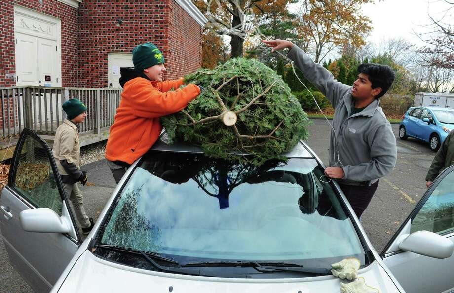 Boy Scouts Milan Radulovich, 12, left, and Mohith Mothukuri, 16, tie a tree to the roof of a car during Troop 82 of Fairfield's annual Christmas Tree and Wreath sale at First Church Congregational in Fairfield, Conn. on Saturday, Nov. 26, 2016. Photo: Christian Abraham / Hearst Connecticut Media / Connecticut Post