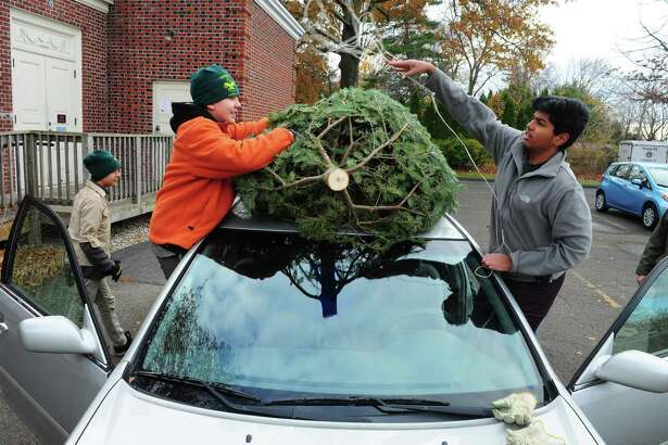 Boy Scouts Milan Radulovich, 12, left, and Mohith Mothukuri, 16, tie a tree to the roof of a car during Troop 82 of Fairfield's annual Christmas Tree and Wreath sale at First Church Congregational in Fairfield, Conn. on Saturday, Nov. 26, 2016.