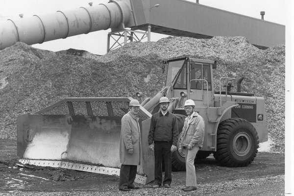 Bernard A. Bartos, SECO project manager, left, Ian R. O'Neil, operations manager, and Phillip G. Sworden, manager of Dow Corning's Natural Resources Team, stand in front of a woodchip dozer. The 30-foot high woodchip pile and the belt conveyor system are in the background. January 1983