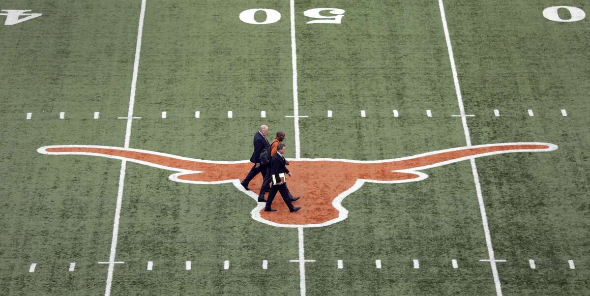Tom Herman, center, walks across the Texas logo at Texas Memorial Stadium with associate athletic director Arthur Johnson, front, and Athletic director Mike Perrin, rear, before a news conference where he was to be introduced as Texas' new head football coach, Sunday, Nov. 27, 2016, in Austin. (AP Photo/Eric Gay)