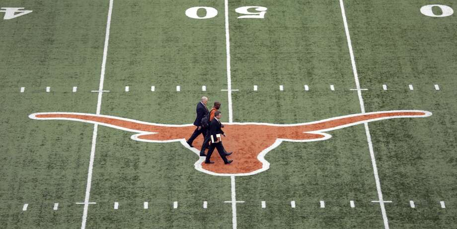 Tom Herman, center, walks across the Texas logo at Texas Memorial Stadium with associate athletic director Arthur Johnson, front, and Athletic director Mike Perrin, rear, before a news conference where he was to be introduced as Texas' new head football coach, Sunday, Nov. 27, 2016, in Austin. (AP Photo/Eric Gay) Photo: Eric Gay/Associated Press