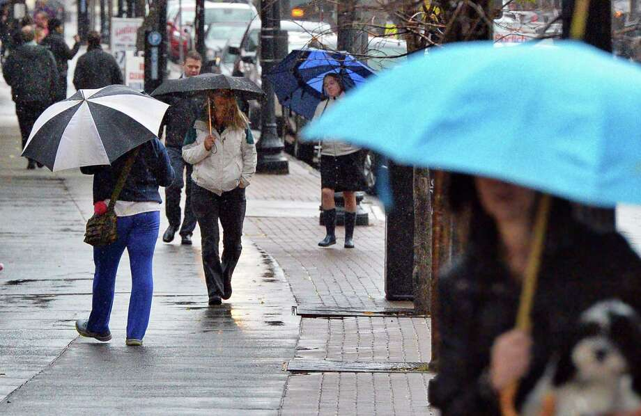 Pedestrians along Pearl Street use umbrellas to fend off a cold rain Tuesday Nov. 29, 2016 in Albany, NY.  (John Carl D'Annibale / Times Union) Photo: John Carl D'Annibale