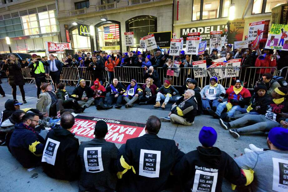 A crowd of about 350 protesters stand on Broadway in front of a McDonald's restaurant, Tuesday, Nov. 29, 2016, in New York. About 25 of the chanting minimum-wage protesters, foreground, were arrested. The event was part of the National Day of Action to Fight for $15. The campaign seeks higher hourly wages, including for workers at fast-food restaurants and airports. (AP Photo/Mark Lennihan) Photo: Mark Lennihan, STF / Copyright 2016 The Associated Press. All rights reserved.