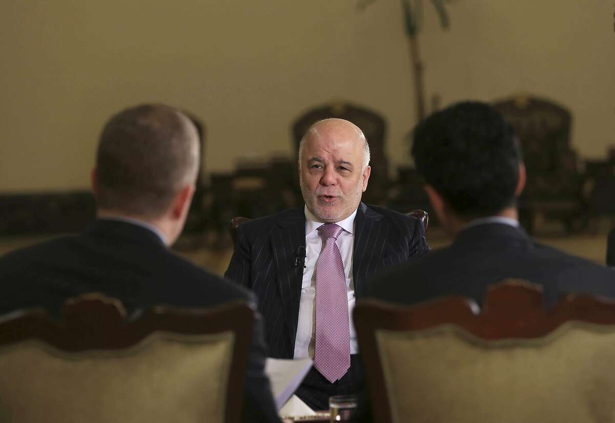 Iraq's Prime Minister Haider al-Abadi, center, speaks during an interview with the Associated Press in Baghdad, Iraq, Monday, Nov. 28, 2016. Al-Abadi said Islamic State fighters lack the �gut