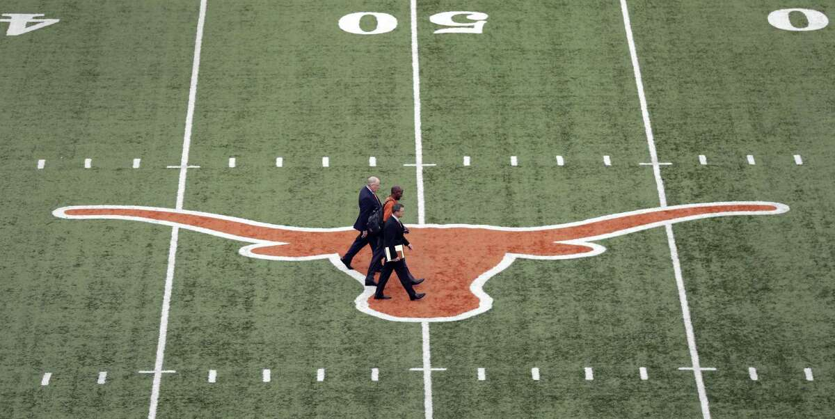 Tom Herman (center) walks across the Longhorns logo at Royal-Memorial Stadium in Austin with UT associate athletic director Arthur Johnson (front) and athletic director Mike Perrin (rear) before a news conference where he was to be introduced as the school's new head football coach on Nov. 27, 2016, in Austin.
