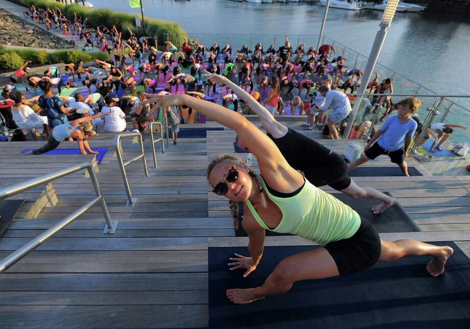 Lauren Cardarelli of Stamford joins in with yoga enthusiasts as Megan Kuczynski of Exhale leads the group during the fourth annual Yoga Jam on the boardwalk at Harbor Point in Stamford. The Give Back Yoga Foundation has created a web-based yoga service training tool to help people find ways to serve others through yoga, with the help of Stratford-based Dot Think Design. Photo: Matthew Brown / Hearst Connecticut Media / Stamford Advocate