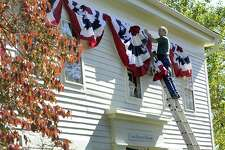"""Michael Bird puts up American Flag bunting at the Gunn Memorial Historical Society and Museum in Washington, Conn. Friday, Oct. 14, 2016. Bird says the museum is preparing for a sneak preview of a permanent exhibit featuring people """"who make this little small town unique."""""""