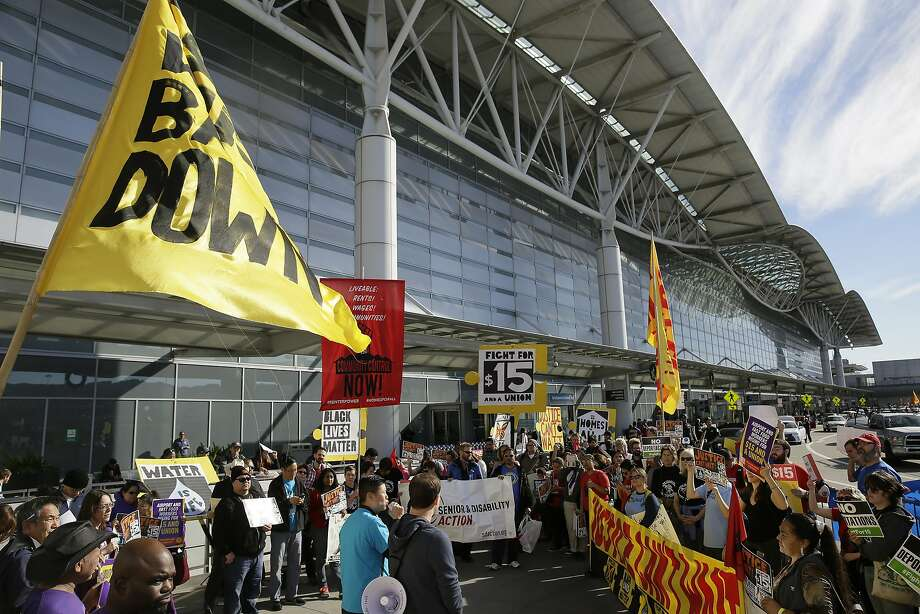 Workers demonstrate for a $15 minimum wage at San Francisco International Airport Tuesday, Nov. 29, 2016, in San Francisco. Fast-food restaurant workers and home and child-care workers rallied in cities including Chicago, Detroit, Los Angeles and New York on Tuesday morning. More protests were expected later in the day. (AP Photo/Eric Risberg) Photo: Eric Risberg, Associated Press