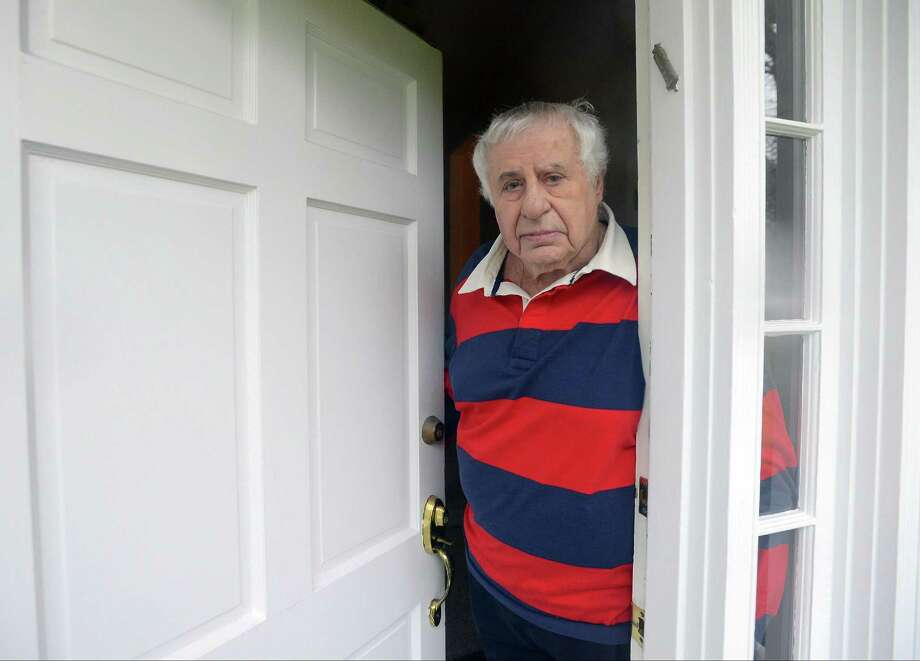 Merlin Alper is photographed in the doorway of his home on Davenport Ridge Lane in Stamford on Nov. 29, 2016.  Alper, like many of his neighbors are talking about the big ugly pipe now running across their lawns. Aquarion installed the pipe to bring 4 million gallons of water a day into Stamford from Bridgeport. The Stamford reservoirs are less than half what they should because of the drought. Photo: Matthew Brown / Hearst Connecticut Media / Stamford Advocate