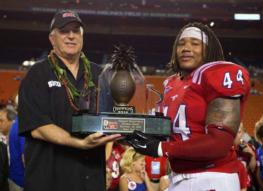 SMU coach June Jones and linebacker Taylor Reed (44) hold the Hawaii Bowl trophy after SMU defeated Fresno State 43-10 in the college football game Monday, Dec. 24, 2012, in Honolulu. (AP Photo/Eugene Tanner) Photo: Eugene Tanner, FRE / FR168001 AP