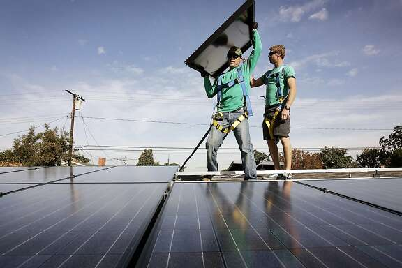 "Joey Ramirez, left, and Taran Stone with SolarCity install solar modules on the roof of a Long Beach, Calif., home. Florida ""has a ton of sunshine, a ton of rooftops,"" a SolarCity spokesman said. ""But there is no rooftop solar industry in Florida."" (Al Seib/Los Angeles Times/MCT)"