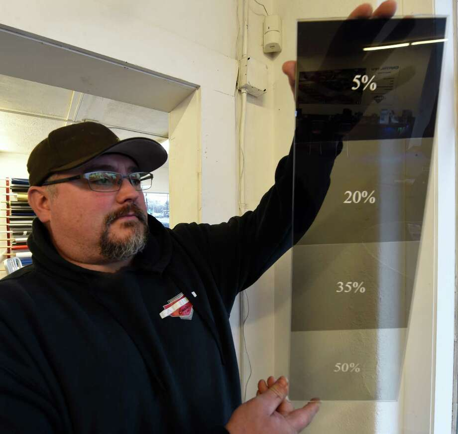 Shawn Denue, Owner of Fat Body Customs, shows a graded tint display which is used to determine what a client wants when tinting the windows of their vehicles on Tuesday, Nov. 29, 2016, in Colonie, N.Y.  Gov. Cuomo approved a bill that will require an examination of tinted or shaded windows during annual vehicle inspections.  (Skip Dickstein/Times Union) Photo: SKIP DICKSTEIN