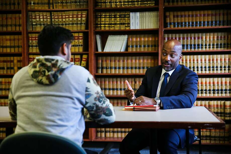 Alameda County Public Defender Brendon Wood (right) speaks with a defendant (who wished to remain anonymous) during an interview about his wrongful arrest due to a glitch in the Odyssey software, at the Alameda County Public Defender's office, in Oakland, California, on Tuesday, Nov. 29, 2016. Photo: Gabrielle Lurie, The Chronicle