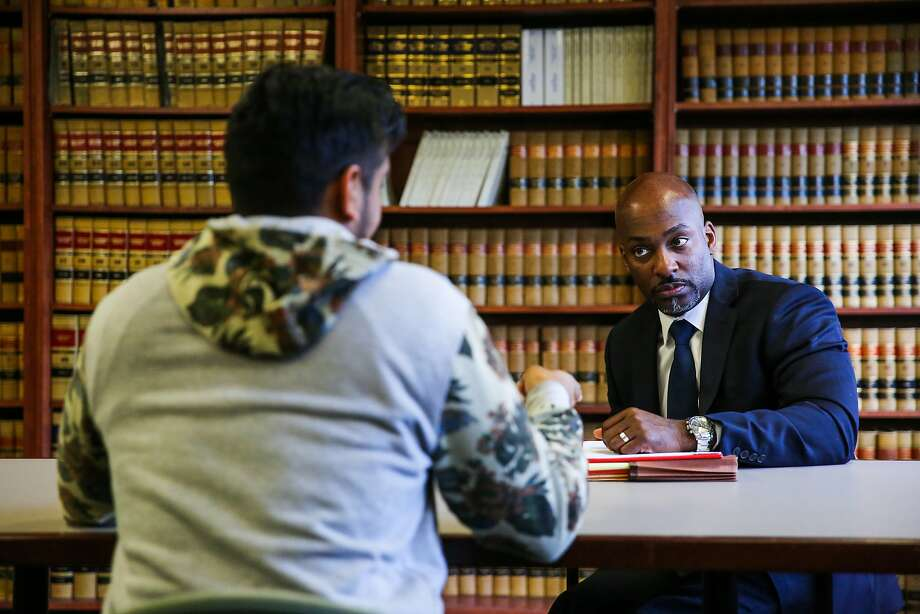 Alameda County Public Defender Brendon Woods (right) speaks with a man wrongfully arrested due to a glitch in the court's new case management system. Photo: Gabrielle Lurie, The Chronicle