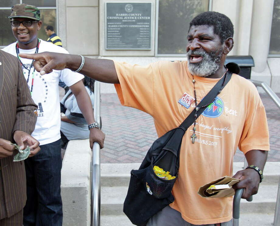 Rick Johnson talks to people infront of the Harris County Criminal Courthouse,1201 Franklin Street, Wednesday, Aug. 24, 2011, in Houston. Johnson has been  a fixture outside the courthouse for atleast ten years where he yells out happy greetings to passers-by as he sells M&Ms and umbrellas and other items. He is now battling colon cancer and courthouse regulars, attorneys, and members of the media are working to help Johnson. Photo: Melissa Phillip, Houston Chronicle / © 2011 Houston Chronicle