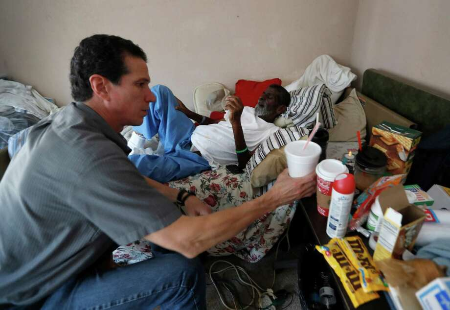 Rick Johnson, in bed in his apartment Tuesday, is visited by KTRK photojournalist Jaime Zamora. Photo: Brett Coomer, Houston Chronicle / 2016 Houston Chronicle