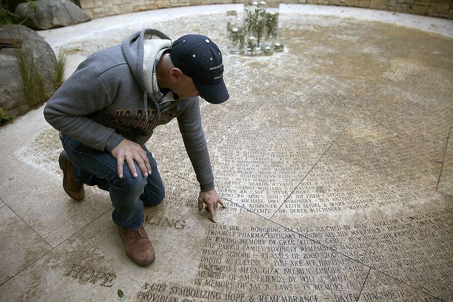 Above: John Cunningham, executive director of the AIDS Memorial Grove on the eastern end of Golden Gate Park, surveys some of the 3,100 engraved names in the Circle of Friends, commemorating people lost to the disease. Photo: Liz Hafalia, The Chronicle