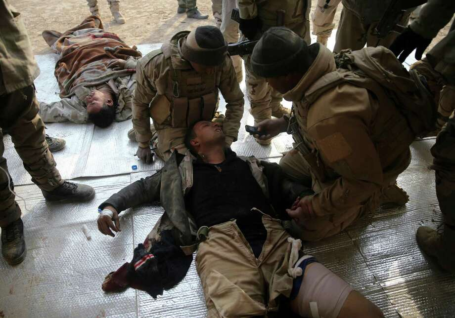Iraqi injured soldiers, who were wounded during the battle against the Islamic State group, lie on the ground as they receive medical treatment. Photo: Hussein Malla, STF / Copyright 2016 The Associated Press. All rights reserved.