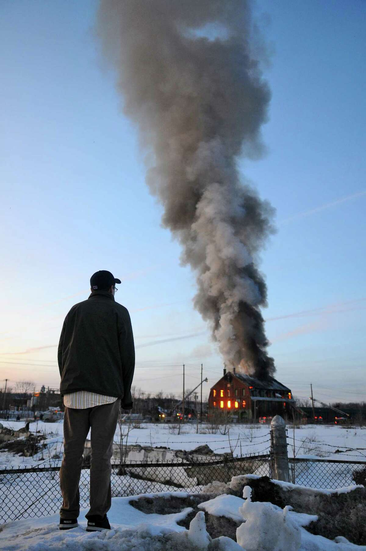 Spectators stand on a snow bank to watch firefighters douse flames on a building at R Kelly Freedman & Son Inc. scrap yard on Thursday evening Mar. 3, 2011 in Green Island, NY. The plume of smoke could be seen from miles away.( Philip Kamrass / Times Union )