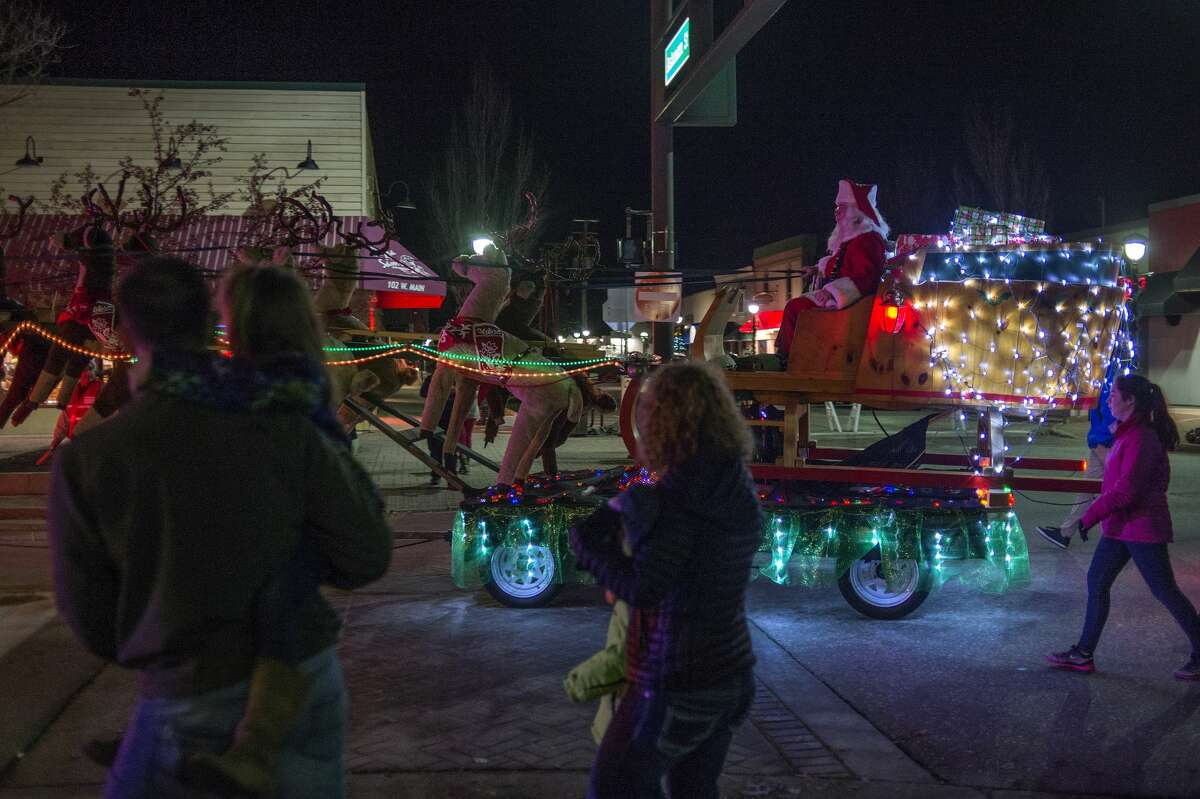 Santa Claus waves to families along Main Street while riding his sleigh to the Midland County Courthouse for the annual lighting ceremony Tuesday evening.
