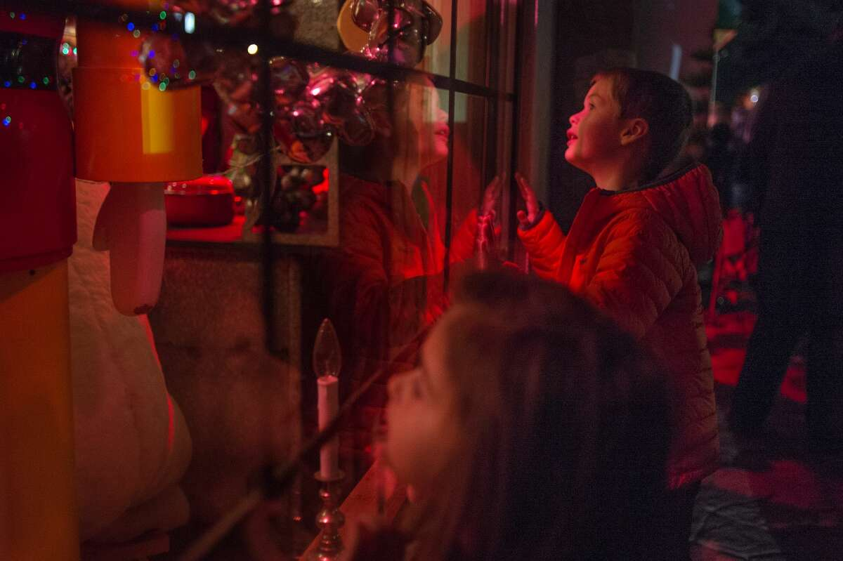 Four-year-old Lauren Truckey, left, and her brother 7-year-old Jackson Truckey, both of Suttons Bay, peer through a window of the Santa House after the annual Midland County Courthouse Lighting Ceremony Tuesday evening. This was the Truckey's first time visiting the Santa House, their mother, Briana Truckey who is originally from Midland, brought them to see Santa and the house.